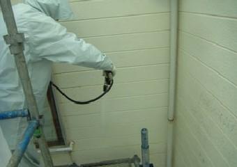 雨合羽を着用し高圧洗浄をする作業員